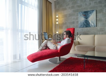 happy young woman relaxing at home and using laptop  - stock photo