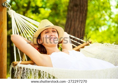 Happy Young Woman Relaxing in a Hammock and Smiling. Hands Behind Head. Summer Nature Daydreaming Concept. - stock photo