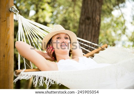Happy Young Woman Relaxing in a Hammock and Smiling. Summer Nature Daydreaming Concept. - stock photo