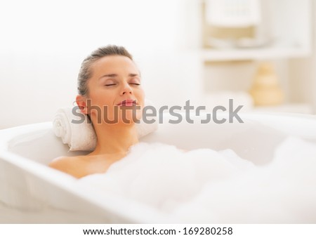 Happy young woman relaxing in bathtub - stock photo