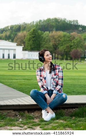 Happy young woman relaxing outside while sitting on wooden alley in the park and listening music - stock photo