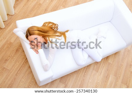 Happy young woman resting at home in a comfortable sofa. - stock photo