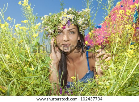 Happy young woman resting in a field - stock photo