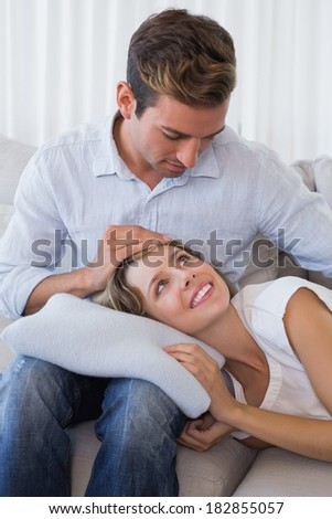 Happy young woman resting on mans lap on couch at home