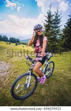 Happy young woman riding a mountain bicycle on the high plateau