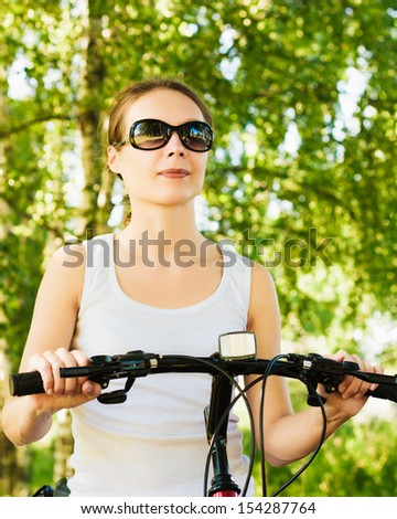 Happy Young Woman riding bicycle outside.