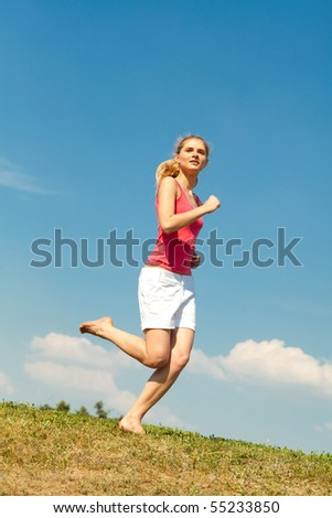 Happy young woman running in field