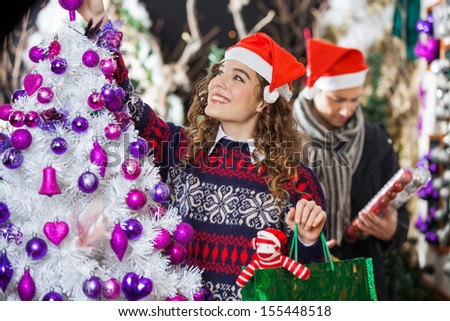 Happy young woman shopping for Christmas decorations with man in store - stock photo