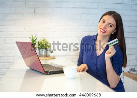 Happy young  woman shopping online with credit card and laptop at home. - stock photo