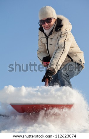 Happy young woman shovelling snow against blue sky - stock photo