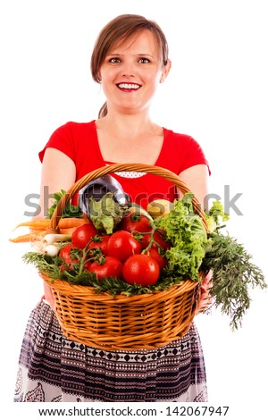 Happy  young woman showing a basket with fresh vegetables isolated on white background