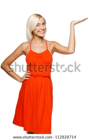 Happy young woman showing a product - empty copy space on the open hand palm, over white background - stock photo