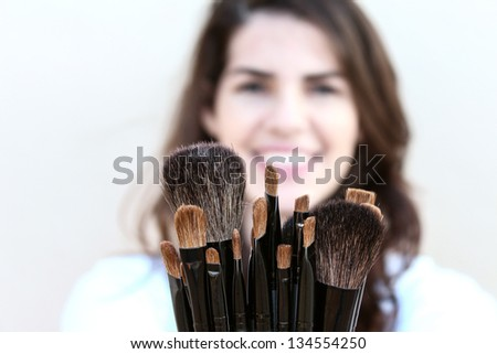 Happy young Woman showing a variety of makeup brushes