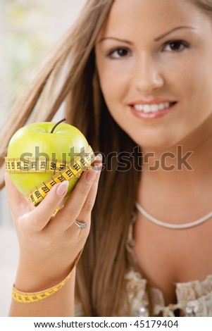Happy young woman showing apple and tape measure, smiling. - stock photo