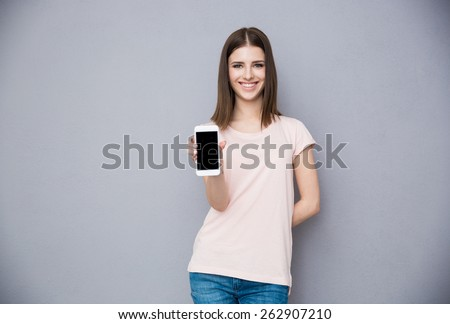 Happy young woman showing blank smartphone screen - stock photo