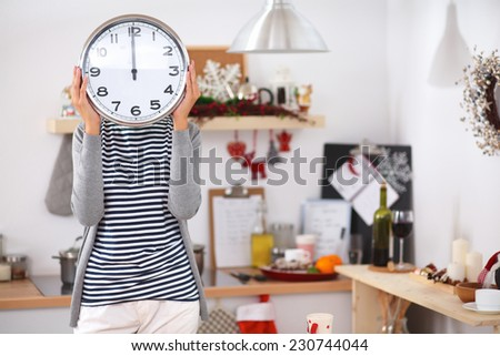 Happy young woman showing clock in christmas decorated kitchen - stock photo