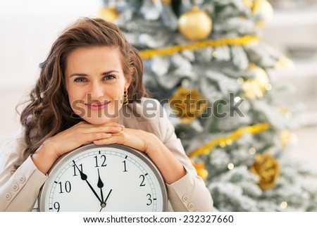 Happy young woman showing clock near christmas tree - stock photo