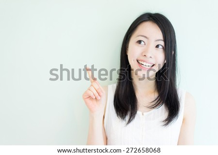 happy young woman showing copy space against light green background - stock photo