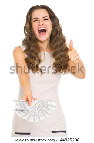 Happy young woman showing fan of dollars and thumbs up
