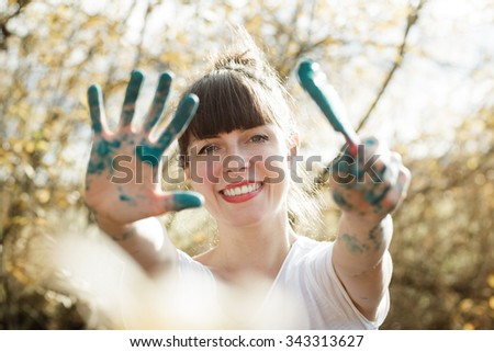 Happy young woman showing her painted hands with blue color in front of blurred trees. Color toned image. Soft autumn back light.
