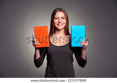 happy young woman showing two books over dark background - stock photo