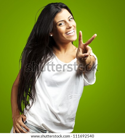Happy Young Woman Showing Victory Sign On Green Background - stock photo