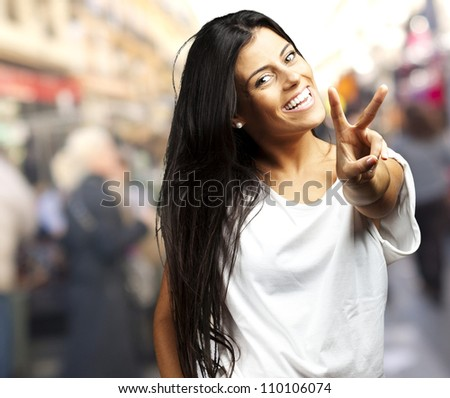 Happy Young Woman Showing Victory Sign, Outdoor - stock photo