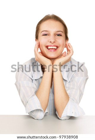 Happy young woman sitting at desk with her chin resting on hands isolated on white background - stock photo
