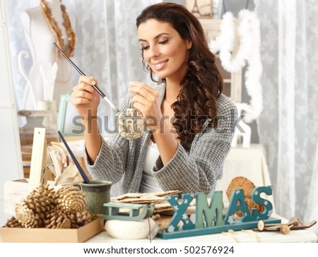 Happy young woman sitting at table, making christmas ornaments, painting at vintage home.