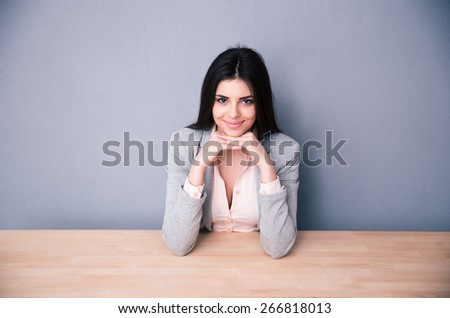 Happy young woman sitting at the table over gray background and looking at camera