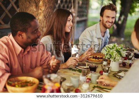 Happy young woman sitting by Thanksgiving table among her friends - stock photo