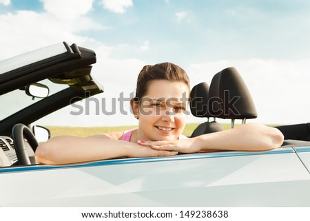 Happy Young Woman Sitting In Her Car