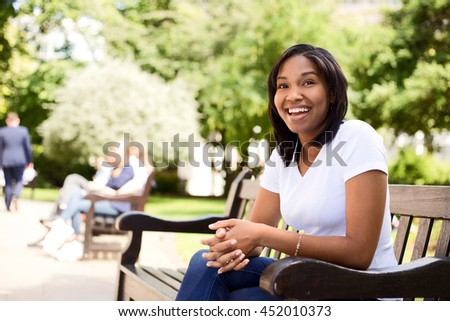 happy young woman sitting on a park bench