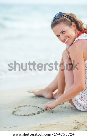 Happy young woman sitting on beach and drawing on sand - stock photo