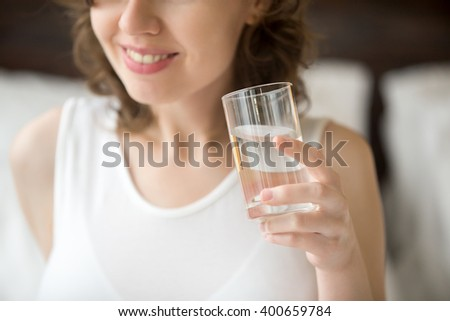Happy young woman sitting on bed drinking water after getting up. Smiling caucasian female model holding transparent glass in her hand. Close-up. Focus on the arm