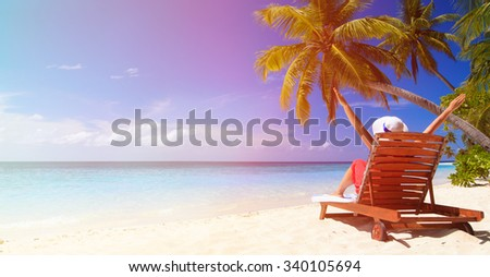 happy young woman sitting on chair at beach, wide panorama - stock photo