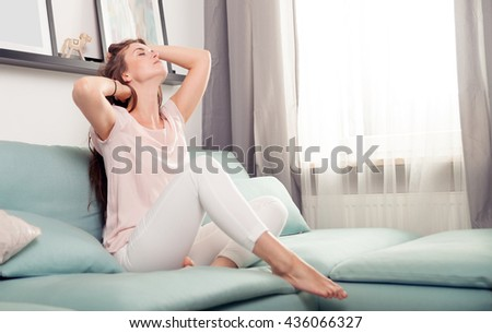 Happy young woman sitting on couch and relaxing at home, casual style indoor shoot
