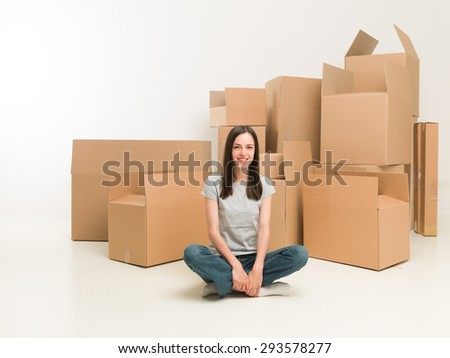 happy young woman sitting on floor surrounded by moving boxes