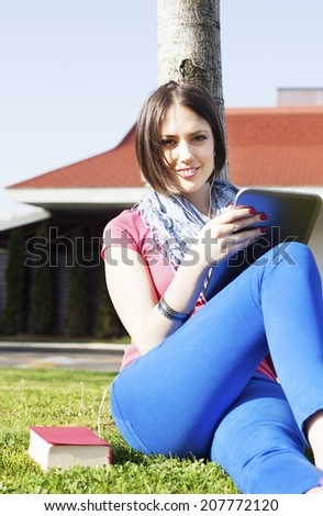 Happy young woman sitting on grass, using digital tablet and listening to music. - stock photo