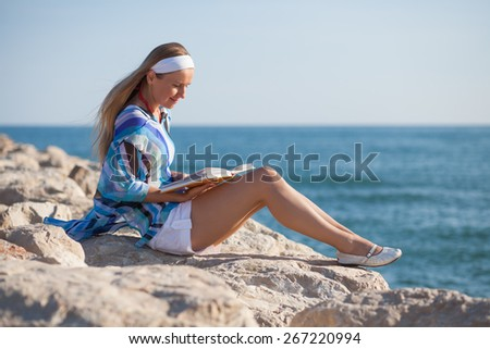Happy young woman sitting on rock and reading a book