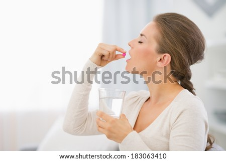 Happy young woman sitting on sofa and taking pill - stock photo