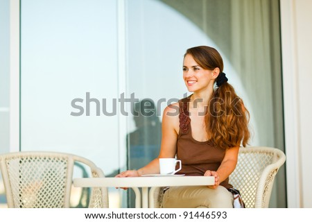 Happy young woman sitting on terrace with cup of tea and looking in corner - stock photo