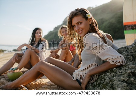 Happy young woman sitting on the beach with her friends in background. Group of friends enjoying on beach holiday.