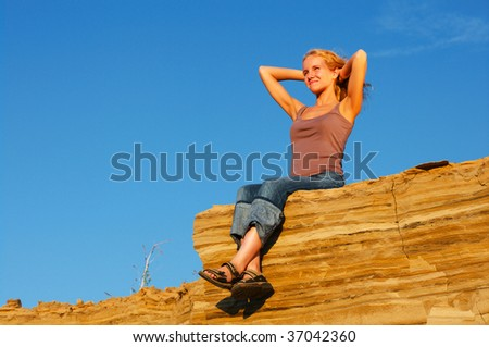 happy young woman sitting on the edge of mountain - stock photo
