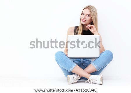 Happy young woman sitting on the floor and using laptop on white background - stock photo