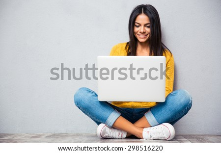 Happy young woman sitting on the floor with crossed legs and using laptop on gray background - stock photo