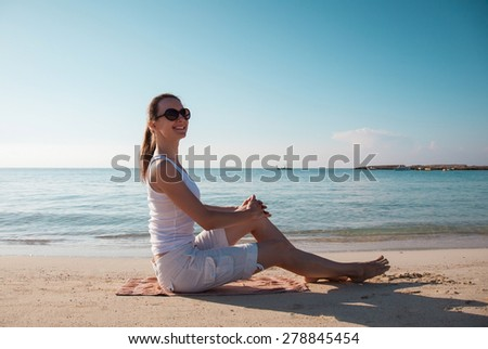 Happy young woman sitting on the sandy beach - stock photo