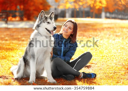 Happy young woman sitting with her dog on grass in park - stock photo
