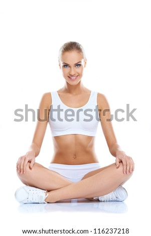 Happy young woman sitting with legs crossed  on isolated white background
