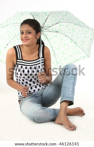 Happy young woman sitting with umbrella isolated on white